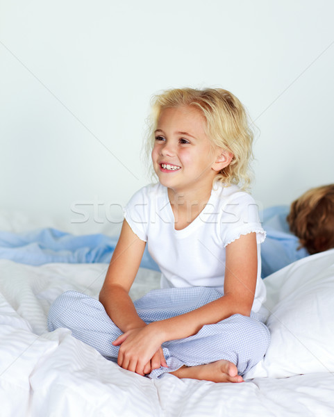 Little girl in bed smiling while her brother is sleeping Stock photo © wavebreak_media
