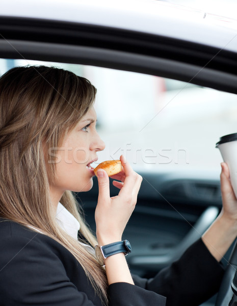 Attractive businesswoman eating and holding a drinking cup while driving to work Stock photo © wavebreak_media