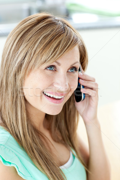 Cheerful woman answering the phone in the kitchen at home Stock photo © wavebreak_media