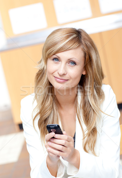 Radiant businesswoman sending a text message with her cellphone at work Stock photo © wavebreak_media