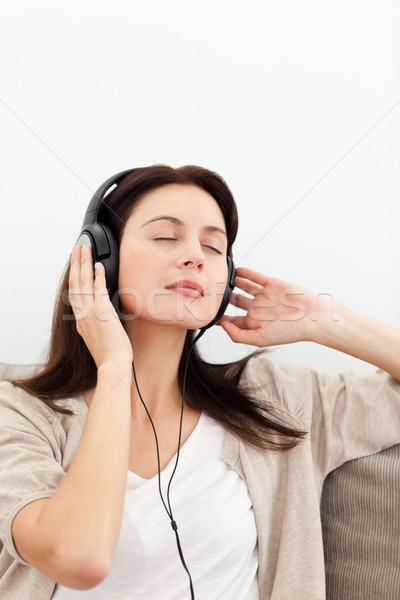 Serene woman listening to the music on the sofa at home Stock photo © wavebreak_media
