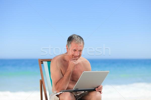 Retired man working on his laptop on the beach Stock photo © wavebreak_media
