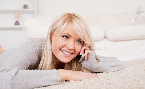 Stock photo: Attractive smiling blond woman talking on cell phone lying down on a carpet in the living room