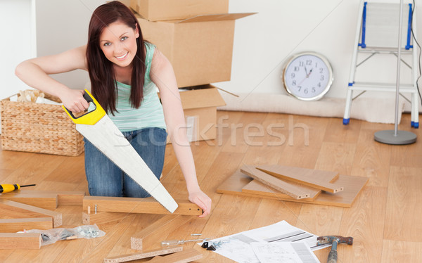 Pretty red-haired woman using a saw for diy at home Stock photo © wavebreak_media