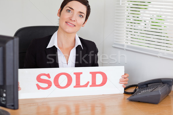 Smiling real estate agent with a sold panel in her office Stock photo © wavebreak_media