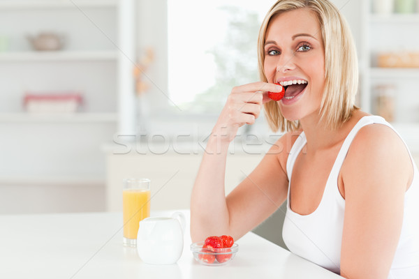Young woman sitting at table eats strawberries in the kitchen Stock photo © wavebreak_media