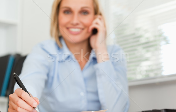 Cute businesswoman on mobile noting something looks into camera in her office Stock photo © wavebreak_media