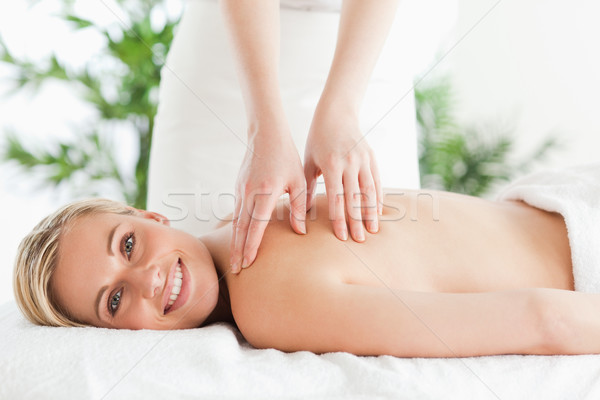 Blonde smiling woman relaxing on a lounger during massage in a wellness center Stock photo © wavebreak_media