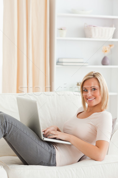 Portrait of a cute woman lying on a sofa with a laptop in her living room Stock photo © wavebreak_media