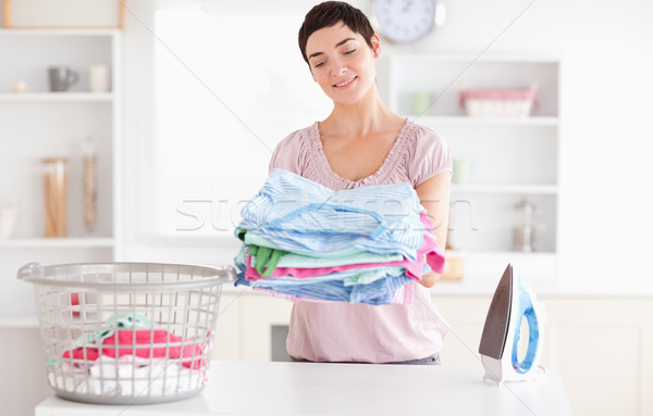 Joyful Woman with a pile of clothes in a utility room Stock photo © wavebreak_media