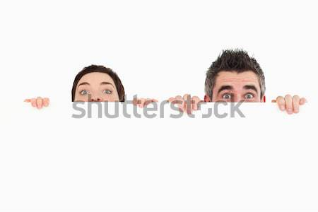 Business partners hiding behind a sign against a white background Stock photo © wavebreak_media