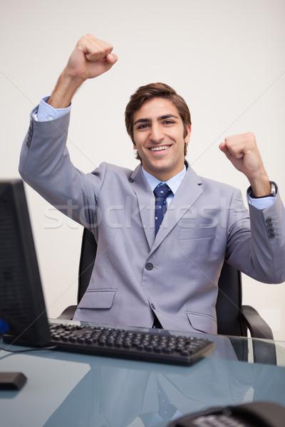 Young businessman raising his fists in success Stock photo © wavebreak_media