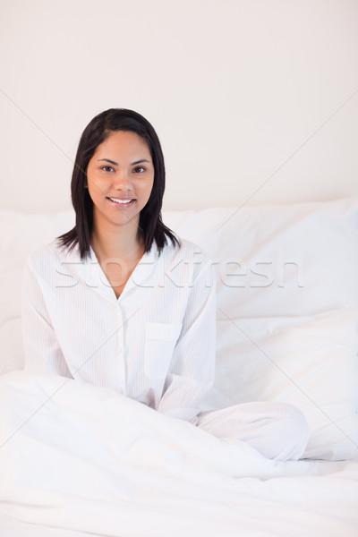 Mosolyog fiatal nő pizsama ül ágy otthon Stock fotó © wavebreak_media