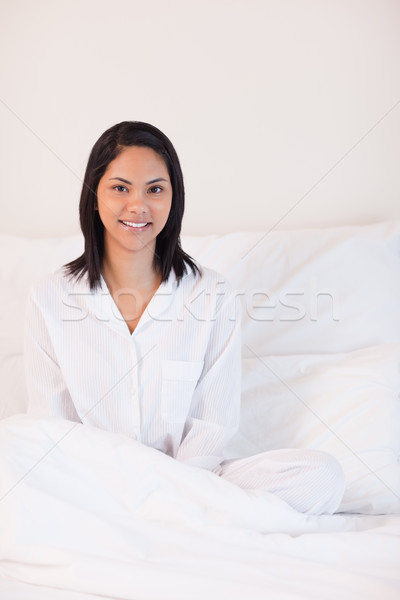 Souriant jeune femme pyjama séance lit maison Photo stock © wavebreak_media