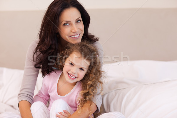 Young mother hugging her daughter on the bed Stock photo © wavebreak_media