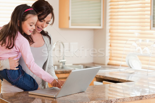 Nina madre usando la computadora portátil cocina Internet portátil Foto stock © wavebreak_media