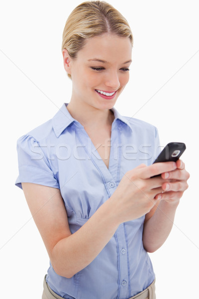 Smiling woman writing text message against a white background Stock photo © wavebreak_media