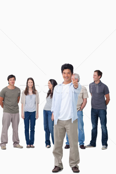 Smiling male giving thumb up with friends behind him against a white background Stock photo © wavebreak_media