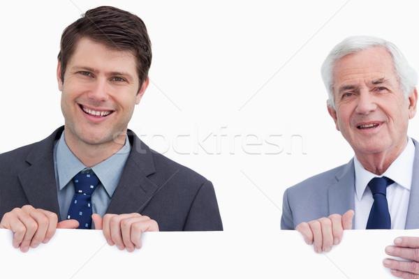 Close up of smiling businessmen holding blank sign against a white background Stock photo © wavebreak_media