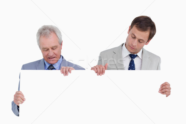 Tradesmen looking at blank sign in their hands against a white background Stock photo © wavebreak_media