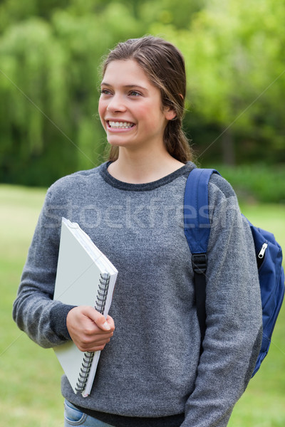 Young girl showing a beaming smile while standing upright and holding a notebook Stock photo © wavebreak_media