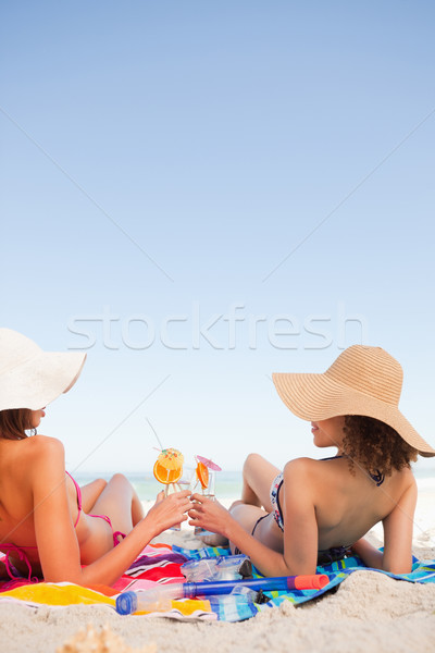 Young women on beach towels clinking their glasses while looking at each other Stock photo © wavebreak_media
