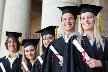 Close-up of five graduates posing in front of the university Stock photo © wavebreak_media
