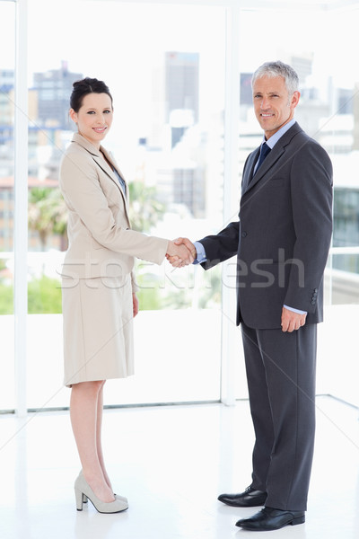 Smiling business people standing upright while warmly shaking hands Stock photo © wavebreak_media