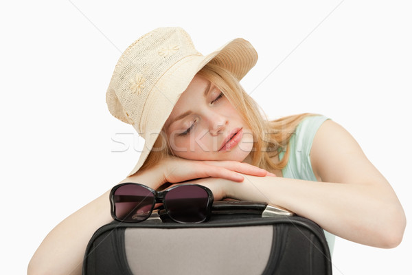 Woman asleep while leaning on a suitcase against white background Stock photo © wavebreak_media