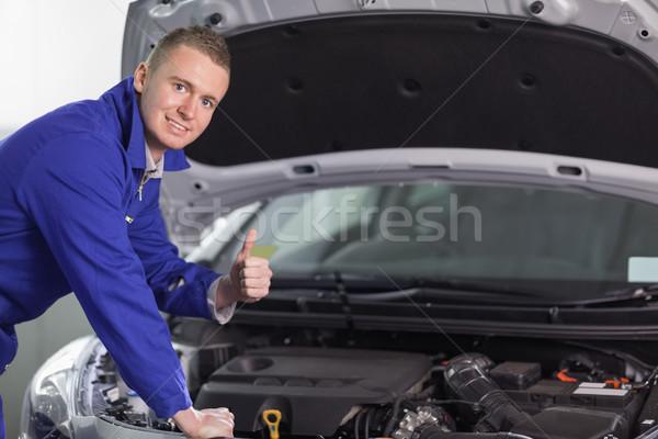 Mecánico mirando cámara pulgar hasta garaje Foto stock © wavebreak_media