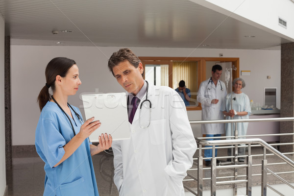 Two doctors standing in the hall of a hospital while looking at documents Stock photo © wavebreak_media