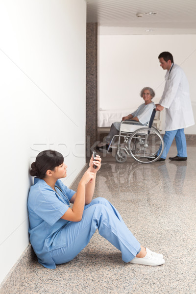 Nurse looking at her mobile phone while sitting in the hallway Stock photo © wavebreak_media