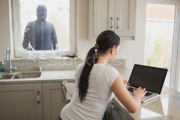 Ladrón mirando mujer cocina usando la computadora portátil ventana Foto stock © wavebreak_media