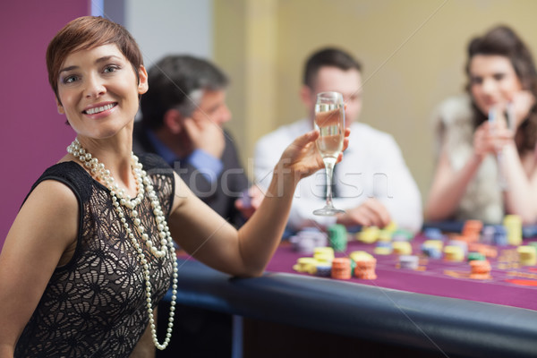 Happy woman with champagne at roulette table Stock photo © wavebreak_media