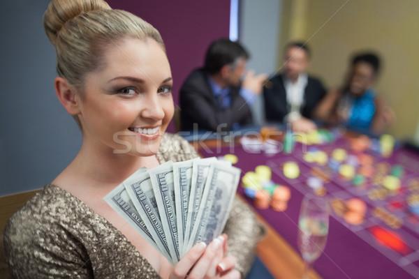 Blonde woman holding fan of dollars in casino Stock photo © wavebreak_media