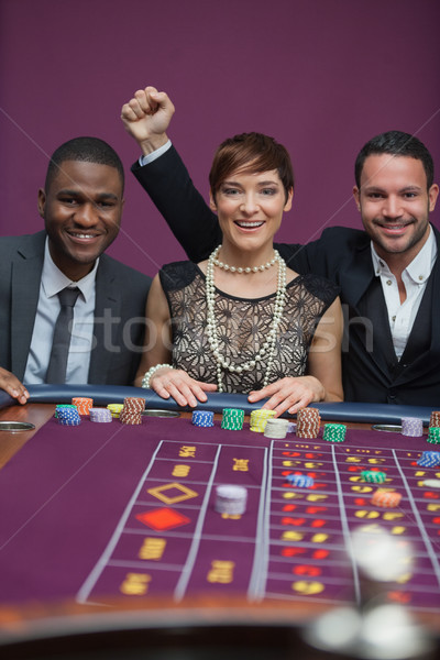 Trois gens heureux roulette table casino femme Photo stock © wavebreak_media