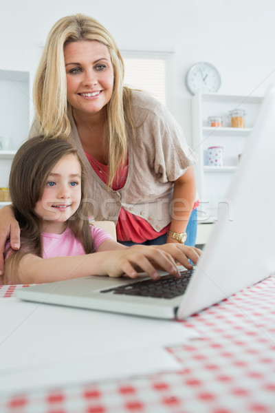Stock photo: Little girl typing with mother watching at laptop in kitchen