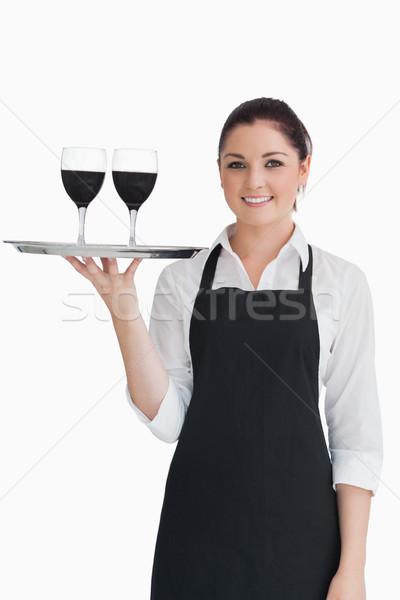 Pretty waitress holding two glasses of wine on a silver tray  Stock photo © wavebreak_media