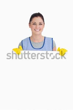 Cheerful maid washing with a sponge on the white background Stock photo © wavebreak_media