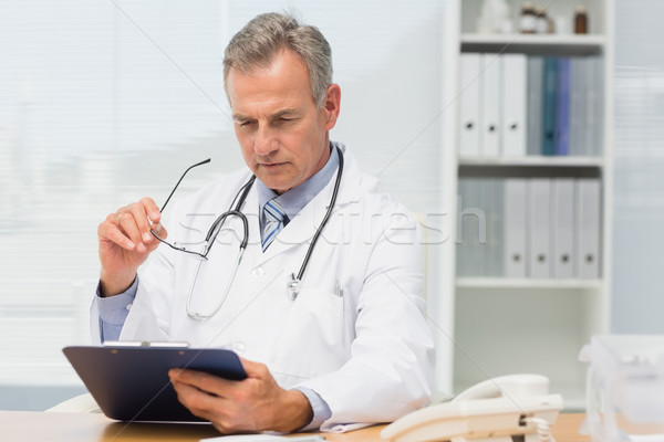 Concentrating doctor sitting at his desk with clipboard Stock photo © wavebreak_media