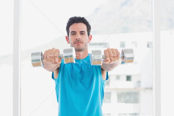 Serious man exercising with dumbbells in fitness studio Stock photo © wavebreak_media