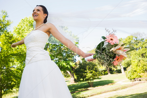 Cheerful young beautiful bride with bouquet in park Stock photo © wavebreak_media