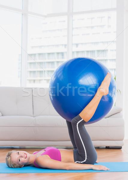 Smiling blonde holding exercise ball between legs Stock photo © wavebreak_media