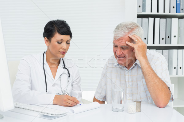 Female doctor with male patient reading reports Stock photo © wavebreak_media