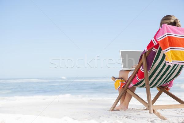 Donna seduta spiaggia deck sedia utilizzando il computer portatile Foto d'archivio © wavebreak_media