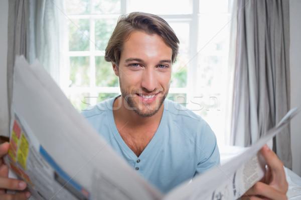 Knap glimlachend man vergadering bed lezing Stockfoto © wavebreak_media
