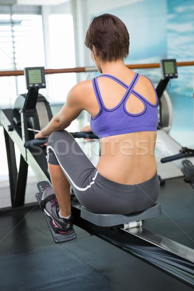 Dopasować brunetka wioślarstwo maszyny siłowni Zdjęcia stock © wavebreak_media