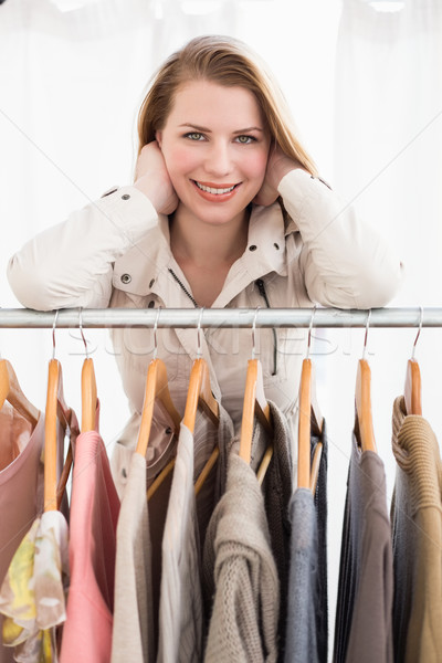 Pretty blonde smiling at camera by clothes rail Stock photo © wavebreak_media