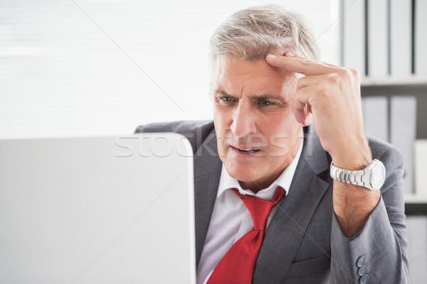 Confundirse empresario mirando portátil oficina negocios Foto stock © wavebreak_media