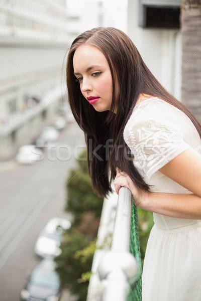 Bastante morena olhando varanda olhando para baixo rua Foto stock © wavebreak_media